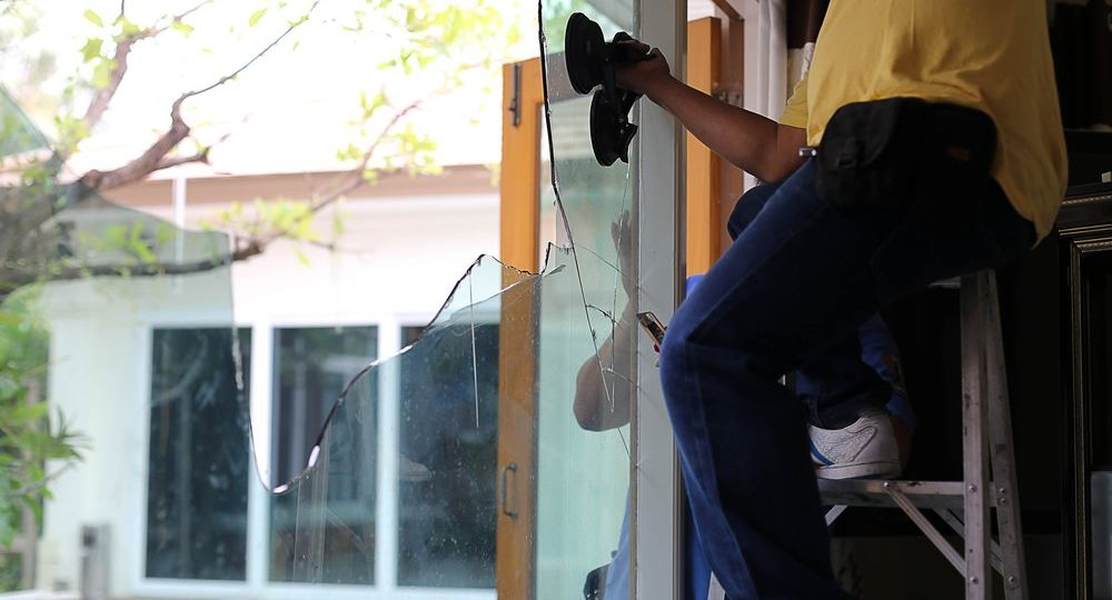 Repair man working on broken glass